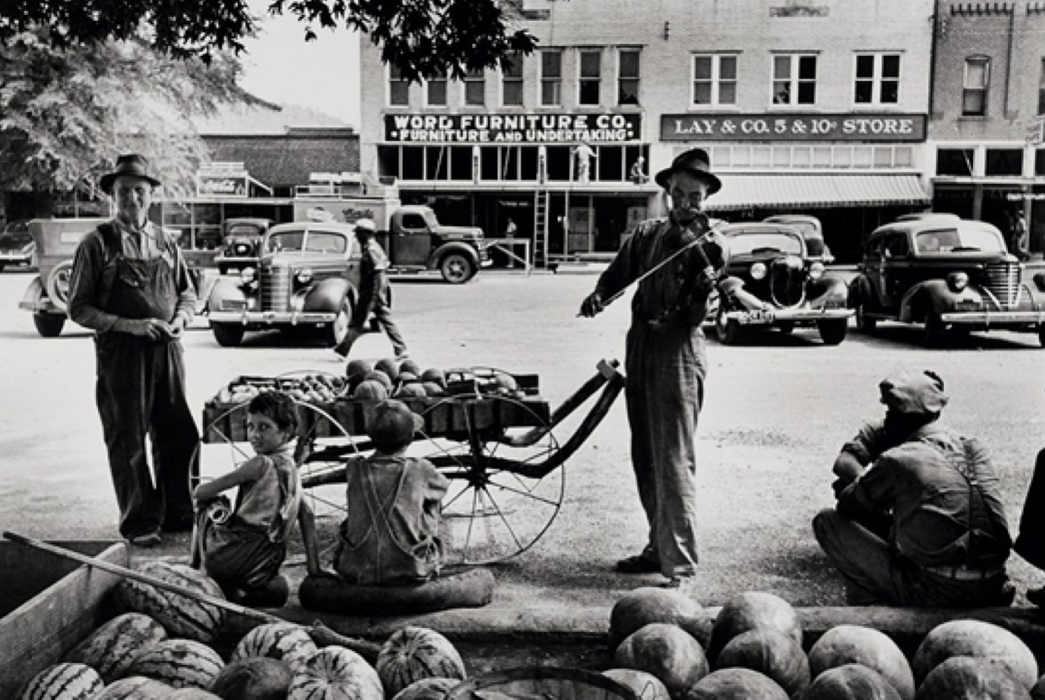 Melon Salesman And Fidler At a Marketplace in Scott, Mississippi